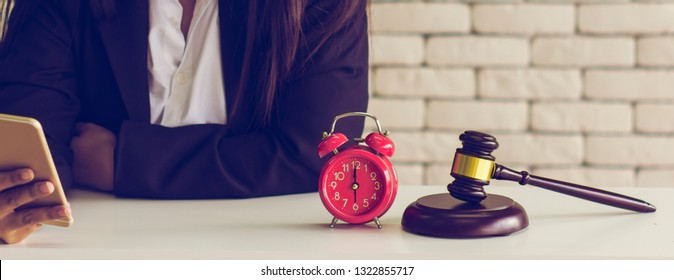 Female auctioneer controls,check list online auction winners, retro alarm clock and golden brown wooden hammer placed on table,online auction business concept,banner panoramic horizontal for header