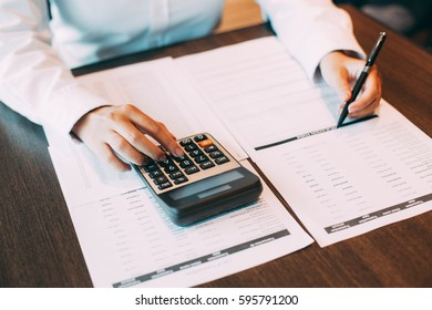 Female auditor checking documents with calculator