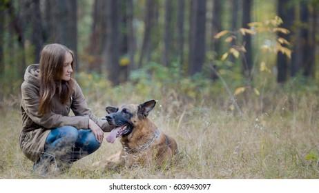 Female in autumn park with her pet - german shepherd