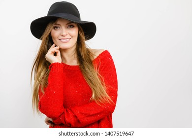 Female autumnal fashion. Woman wearing red sweater black stylish hat, smiling and posing in studio