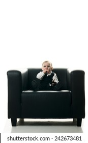 A female baby wearing a dark suit with shirt and tie and sitting in a big black leather chair playing with a cell phone, isolated on white background.