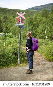 Female with backpack looking at a sign at the walking trail of Kungsleden in Lapland, Sweden.