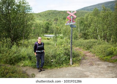Female with backpack standing at a sign at the walking trail of Kungsleden in Lapland, Sweden.