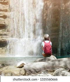 Female backpacker explorer sitting on stone and enjoying view of waterfall, rear view.