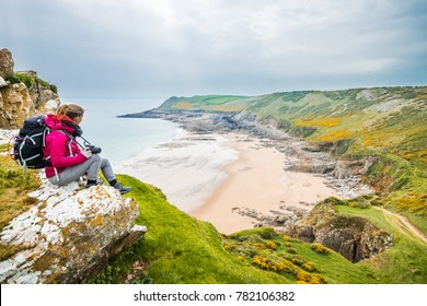 Female Backpacker Looking Into Distance From A Cliff At Rocky Sea Shore On A Cloudy Day In Rhossili, Wales Coast Path
