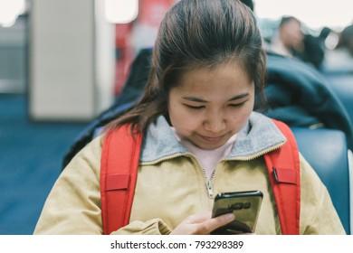 Female backpacker using smartphone and smilling between waiting for boarding in the airport