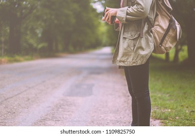 Female backpackers standing on the open road and hold the Bible. The concept goes out to share the gospel.