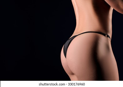 female backside in black panties on dark studio background with space for text