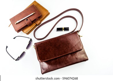 Female bag, glasses, lipstick, notepad and pen not against white background