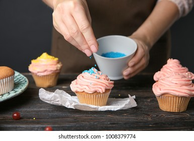 Female baker decorating tasty cupcake with sprinkles at table