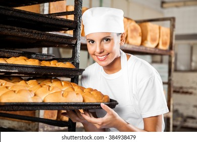 Female Baker Holding Baking Tray By Rack In Bakery