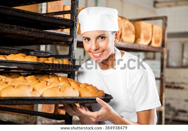 Female Baker Holding Baking Tray By Rack In Bakery