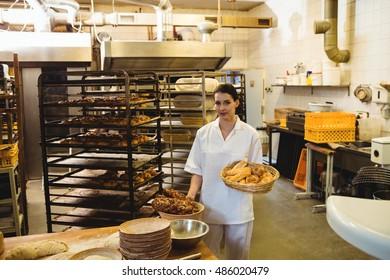 Female baker holding basket of sweet foods at bakery shop