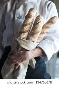 Female baker holding fresh baked French baguette