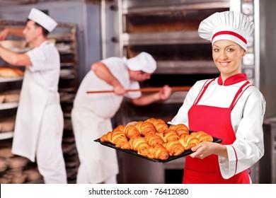 A female baker holding freshly baked croissants in bakery