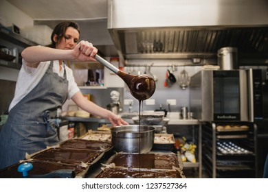 Female baker standing in a kitchen at work. She has a pan of melted chocolate and is using a kitchen utensil pour the chocolate.
