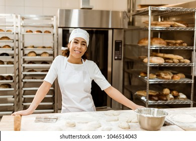 female baker standing at workplace on baking manufacture