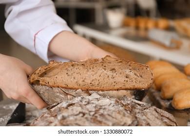 Female baker with tasty fresh bread, closeup
