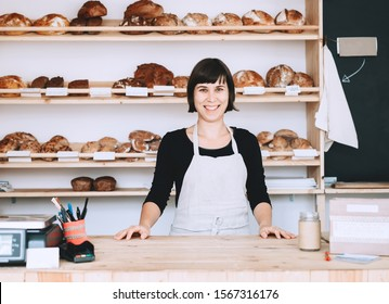 Female bakery worker behind the counter ready to service. Seller of zero waste shop on background of fresh organic homemade bread on wooden shelves in plastic free store. Owner small local business.