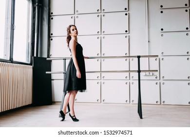 Female ballerina posing at rehearsal. Ballerina in a black dress at the ballet machine