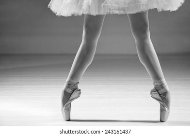 Female ballerina standing on toes in ballet shoes, low section. Grayscale image.