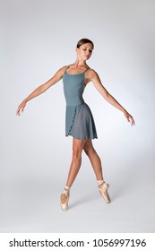 Female ballet dancer in gray leotard and en pointe, isolated in light gray background