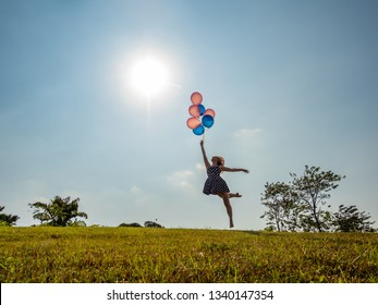 Female ballet dancer holding balloons flying away