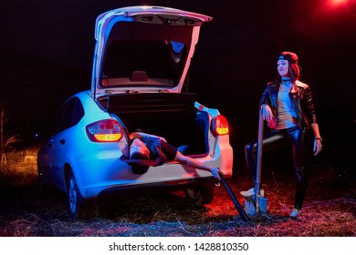 Female bandit near the car with a shovel and a dead or drunk guy in the trunk at night time and colored red and blue light. Photoshoot about life of gungsters in Russia