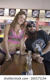 Female bar tender posing with motorcycle man at the 67th Annual Sturgis Motorcycle Rally, Sturgis, South Dakota, August 6-12, 2007