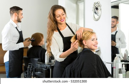 Female barber combing woman's hair at a hair salon
