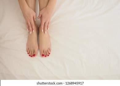 Female bare feet and hands on white bedding, close up. Perl manicure and classic red pedicure. Woman put her fingers on her smooth skin. Skin care and massage concept.