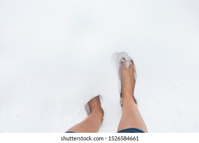female bare feet on a winter frosty day in a snowdrift of snow