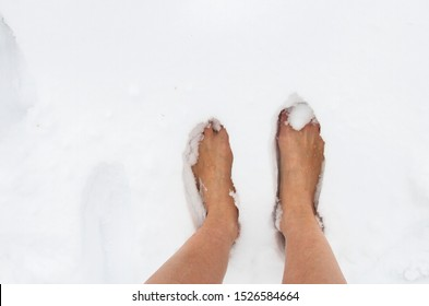 female bare feet on a winter frosty day in a snowdrift of snow, hardening of the body