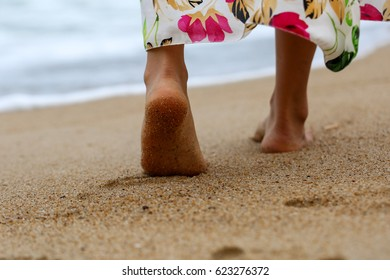 Female bare feet walking on beach sand closeup. Lonely sandy adventure, downshift idea, remote outsource work, path of solitude, wet trace, destination, way, track, trail, tropical print concept