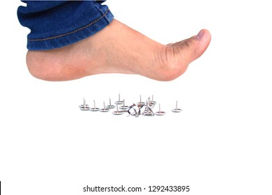 Female bare foot above pushpin, isolated on white background. showing danger concept.