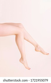 Female bare legs raise, On a beige background. Beauty salon, depilation, care, medicine, varicose veins, cosmetic surgery, spa and treatment concept. vertical photo