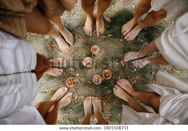 Female barefoot feet on dry grass standing in a circle with glasses of wine in the middle.