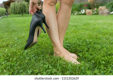 Female barefooted legs on green lawn, woman holding classic heeled shoes. End of the working day, rest, fatigue