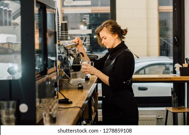 Female barista enjoying working process preparing coffee drinks using professional equipment in cafeteria. Skilled waitress in apron on coffee machine making cappuccino near big window on background.