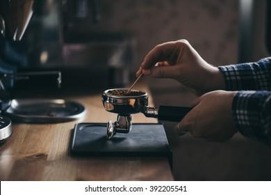 Female barista grooming coffee in a portafilter