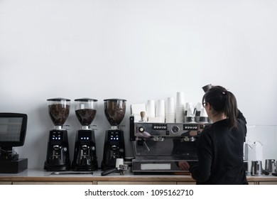 Female barista barista makes coffee in coffee shop