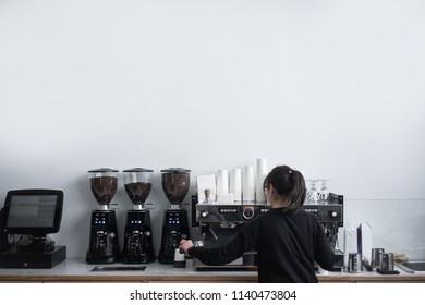 Female barista barista makes coffee in coffee shop