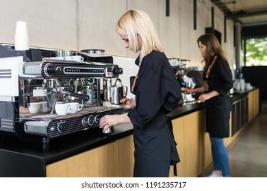 Female barista making espresso coffee.