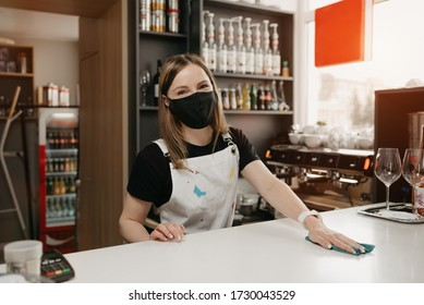 A female barista in a medical black face mask smiles and cleaning the bar counter in a coffee shop. A beautiful waitress disinfecting a cafe while waiting for clients.