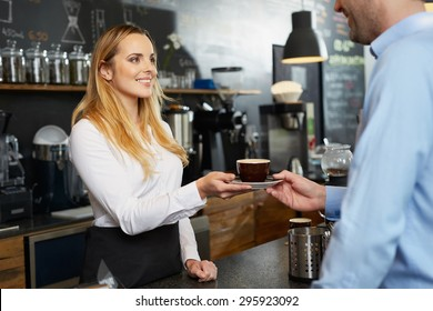 Female barista offering a cup of cappuccino to customer at cafe
