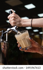 Female barista is pouring nitrogen coffee with blown froth and splashes into a glass on bokeh background