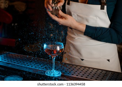Female barman hand spraying blue-colored bitter on the elegant cocktail glass on the bar counter