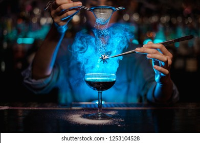 Female bartender adding to a brown cocktail and pour on a flamed badian on tweezers a powdered sugar on the bar counter on the blurred background in the blue light.