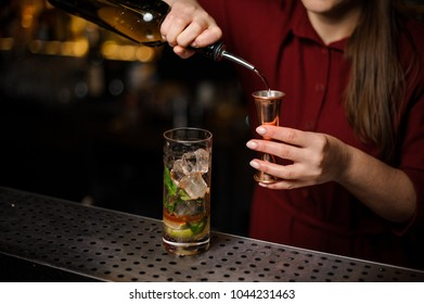 Female bartender filling a liqour to the measuring pile for preparing a delicious fresh cocktail