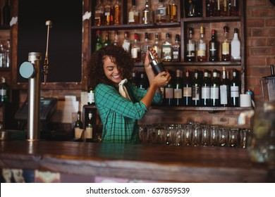 Female bartender mixing a cocktail drink in cocktail shaker at counter